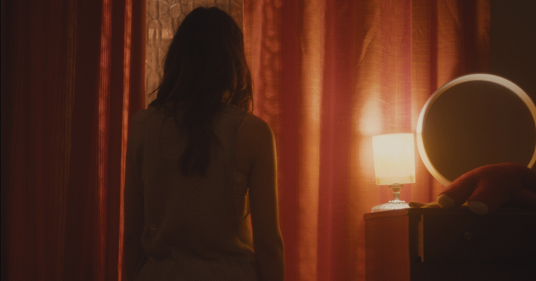 a girl standing in a room with the curtains pulled and a lamp on