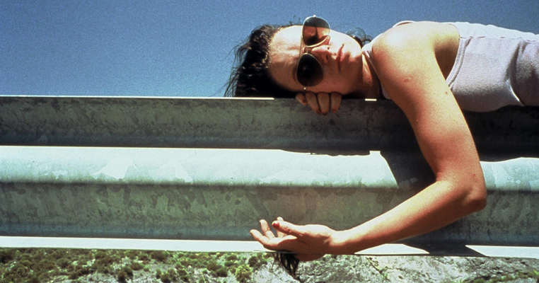a girl lies on a gate wearing sunglasses