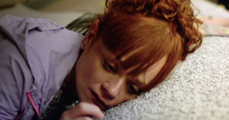 a woman with red hair lays her head on a carpet