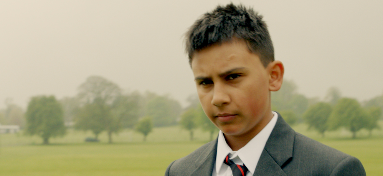a boy in school uniform standing in a field