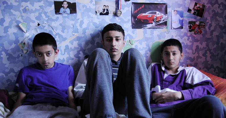 three brothers sit on a bed