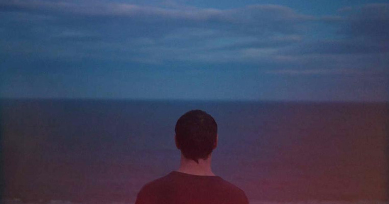 close up of the back of a boys head looking into the sea