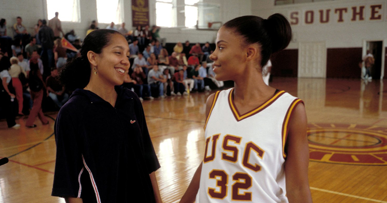 two girls look at each other on a basketball court