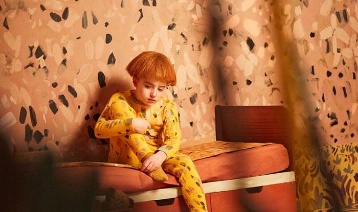 a boy in pyjamas sitting against a painted wall