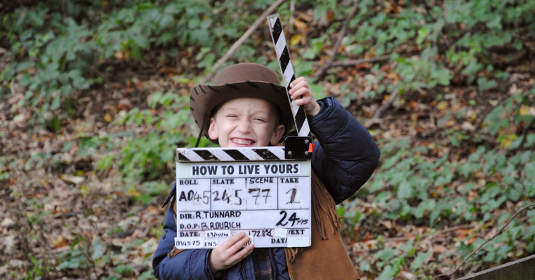 a child on set with a clapper board