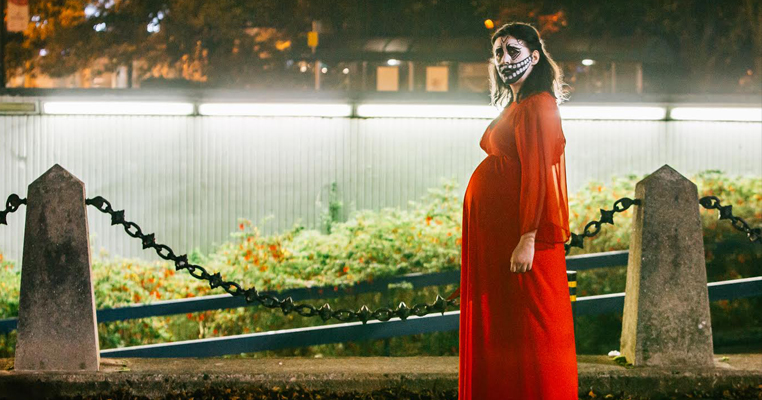 A pregnant woman in a red dress standing outside