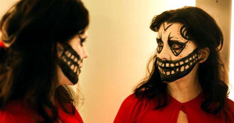 a woman looking in the mirror with facepaint on