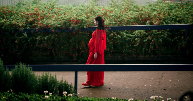 a prenant woman standing a park in a red dress