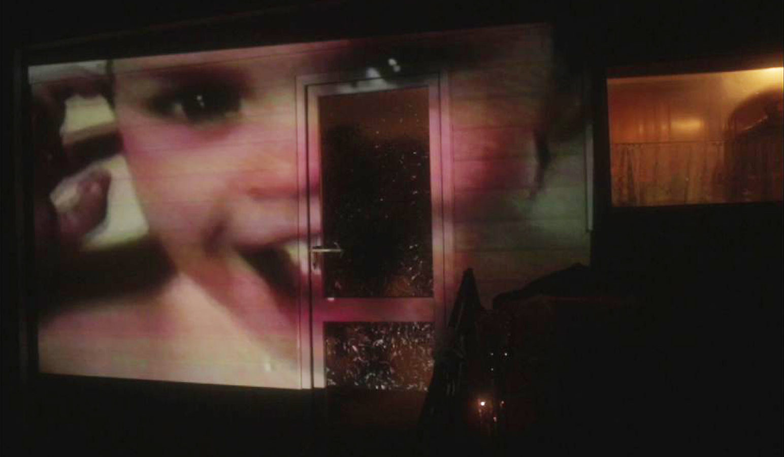 a video of a baby being projected on to a shed in a garden