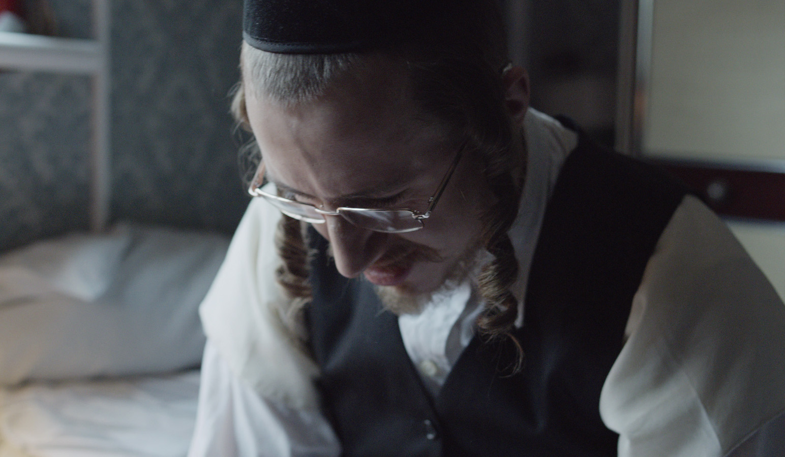 Close up of Hasidic Jewish boy sitting on his bed.