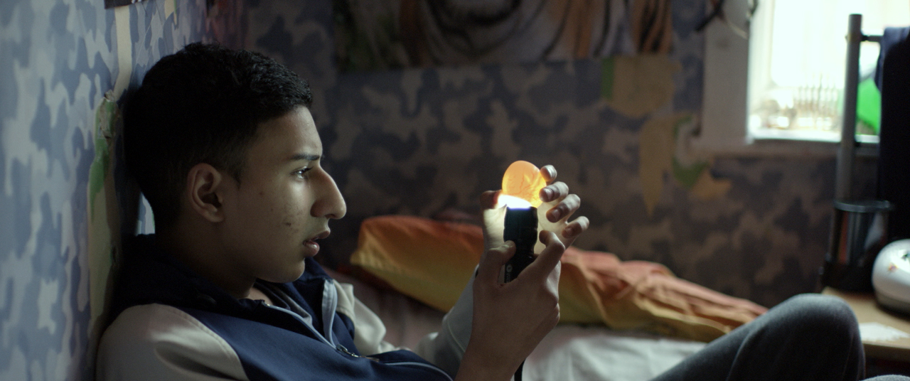 a boy sits on a bed holding a torch under a chicken egg
