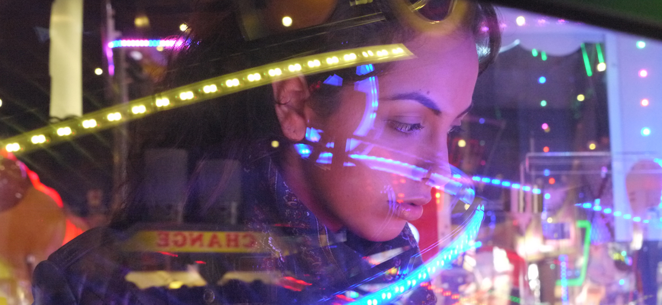 A girl looking into a machine at an arcade