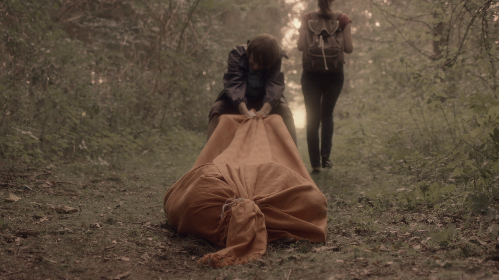 A boy and girl drag a body bag through the woods