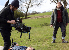 a man lying on the grass in a field with another filming him