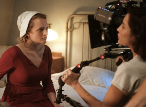 a woman being filmed on a bed