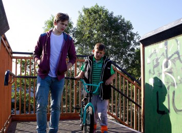a boy on a bike cycling next to an older boy walking across a bridge