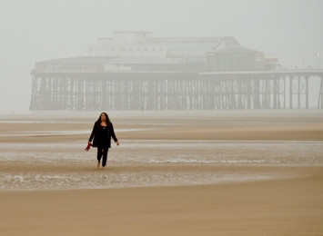 a woman on a beach on a cloudy day