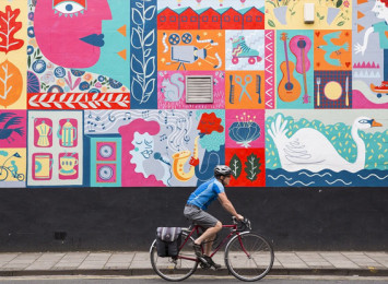 a man on bicycle riding past a graffiti'd wall