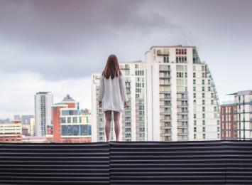 a girl stands on the edge of the top of a building with other tall buildings around her