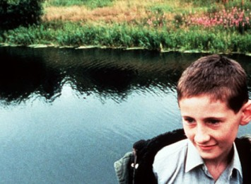 a boy smiles alone in front of a lake
