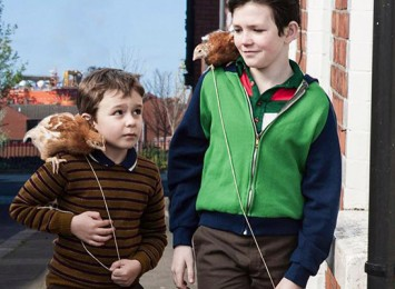 two boys walk down the street holding chickens