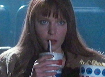 close up of a lady in the cinema with popcorn and drink
