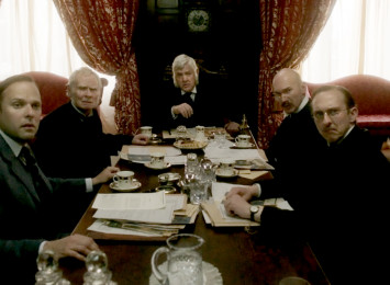 several middle aged white men sitting around a table in a 1920's period setting