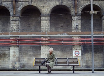 A elderly lady sits on a bench on the London underground waiting for a train to arrive.