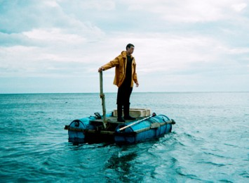 a boy standing on a raft in the middle of the sea