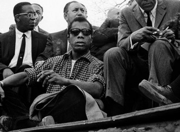 a man with sunglasses on sitting with a a few other men around him, with the bright sky behind them