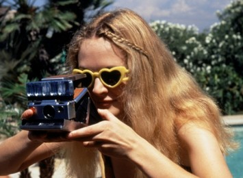 a blonde woman looks into a Polaroid camera