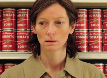 A woman stands in a shopping aisle with soup cans behind her