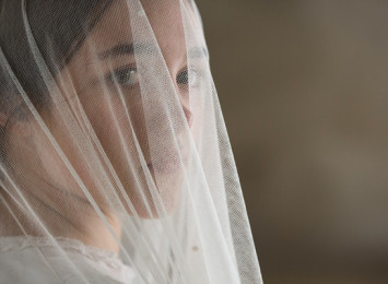 A young girl with a veil over her head