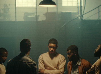 five young men stand in a circle talking