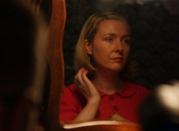 a woman looking in the mirror wearing red