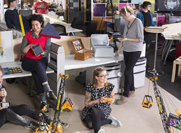 people sitting in an office with remote control cranes