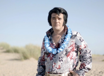 A man standing by sand in an Elvis costume
