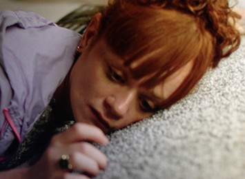 A red head lady lies on a carpet