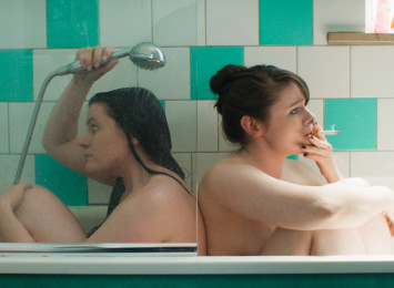 two girls sitting down in a bath showering (conjoined twins)