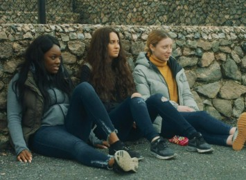 three girls sitting on the ground against a stone wall