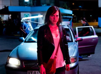 a woman in front of a car with red lights on her face