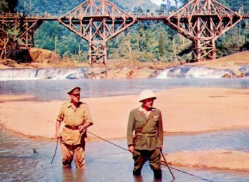two men stand in a river