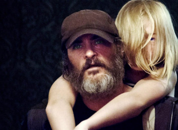 a man in darkness with a beard giving a small blonde girl a piggy back