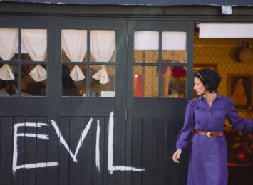 a women stands outside her shop with the word EVIL spray painted onto it.