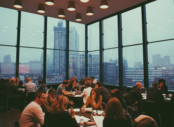 people sitting aorund tables in a room with walls made of glass