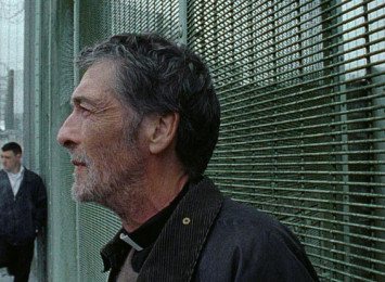 a man stands against a metal fence