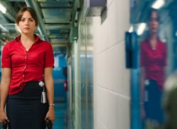a girl standing in a hallway in a red top