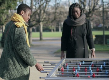 two girls are playing table football outside in a park