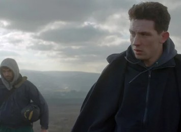 two men in a field with a moody sky