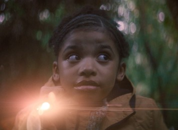 A young girl holding a flashlight wonders through the woods